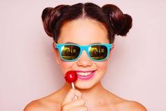 Chica joven con las gafas de sol y la piruleta Foto de archivo libre de regalías