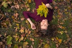 Chica joven con las hojas en otoño Fotos de archivo libres de regalías