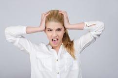 Chica joven con las manos en su cabeza que es griterío desesperado. Fotografía de archivo libre de regalías