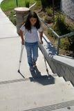 Chica joven con las muletas en los pasos de progresión Fotos de archivo libres de regalías