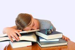 Chica joven con las pecas que duerme en los libros Foto de archivo libre de regalías
