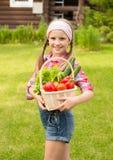 Chica joven con las verduras en cesta Imagen de archivo libre de regalías