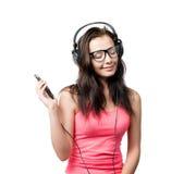 Chica joven con los auriculares en el fondo blanco Fotografía de archivo libre de regalías