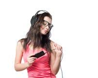 Chica joven con los auriculares en el fondo blanco Imagen de archivo libre de regalías