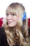 Chica joven con los auriculares en el sofá rojo Foto de archivo
