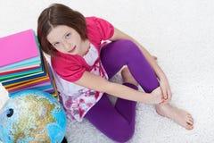Chica joven con los libros de escuela y el globo de la tierra Fotografía de archivo libre de regalías