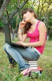 Chica joven con los libros y la computadora portátil Fotos de archivo