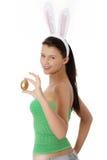 Chica joven con los oídos del conejito que sostienen el huevo de oro Foto de archivo libre de regalías