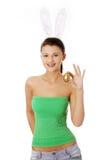 Chica joven con los oídos del conejito que sostienen el huevo de oro Fotos de archivo libres de regalías
