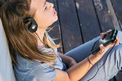 Chica joven con los ojos cerrados que disfruta de música al aire libre con auriculares y un smartphone Imagen de archivo libre de regalías