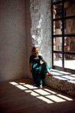Chica joven con los ojos cerrados que se colocan cerca de la ventana en casa y que disfrutan de la luz caliente del sol fotografía de archivo