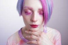 Chica joven con los ojos y el pelo del rosa, como una muñeca Imágenes de archivo libres de regalías