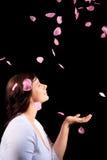 Chica joven con los pétalos color de rosa Fotos de archivo libres de regalías