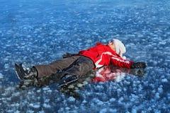 Chica joven con los patines que descansan sobre el lago congelado Imagenes de archivo