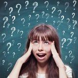 Chica joven con los signos de la expresión que preguntan y de interrogación Fotografía de archivo