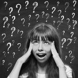 Chica joven con los signos de la expresión que preguntan y de interrogación arriba Fotos de archivo libres de regalías