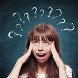 Chica joven con los signos de la expresión que preguntan y de interrogación arriba Imagenes de archivo