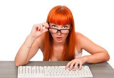 Chica joven con los vidrios que mecanografía el teclado Imagenes de archivo