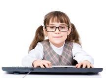 Chica joven con los vidrios que mecanografía el teclado Aislado en blanco Foto de archivo