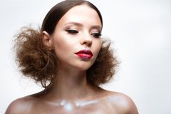 Chica joven con maquillaje brillante creativo y piel brillante Modelo hermoso con un peinado, flechas en ojos y labios del rojo B Imagen de archivo libre de regalías