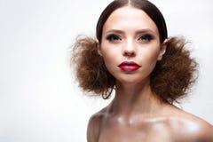 Chica joven con maquillaje brillante creativo y piel brillante Modelo hermoso con un peinado, flechas en ojos y labios del rojo B Fotografía de archivo