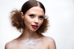 Chica joven con maquillaje brillante creativo y piel brillante Modelo hermoso con un peinado, flechas en ojos y labios del rojo B Foto de archivo libre de regalías