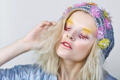 Chica joven con maquillaje del colorfull en sombrero chispeante Foto de archivo