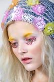 Chica joven con maquillaje del colorfull en sombrero chispeante Fotos de archivo