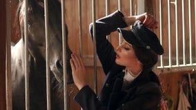 Chica joven con maquillaje profesional en una granja del pueblo cerca de un caballo marrón metrajes