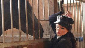 Chica joven con maquillaje profesional en una granja del pueblo cerca de un caballo marrón almacen de metraje de vídeo