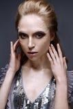 Chica joven con maquillaje y texturas creativos en su cara Modelo hermoso en un vestido de la lila con las chispas Fotos de archivo