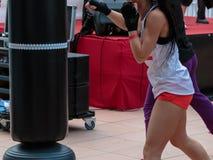 Chica joven con pantalones cortos y top sin mangas blanco: Entrenamiento del boxeo de la aptitud con el saco de arena Imágenes de archivo libres de regalías