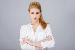Chica joven con parecer cruzado brazos enojado. Foto de archivo