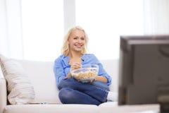 Chica joven con película de observación de las palomitas en casa Imágenes de archivo libres de regalías