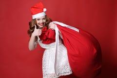 Chica joven con sonrisa encantadora, en el sombrero de Papá Noel, con el bolso grande con los presentes Imagenes de archivo