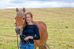Chica joven con su caballo en prado Foto de archivo