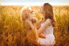 Chica joven con su perro en el campo en luz del sol Fotografía de archivo