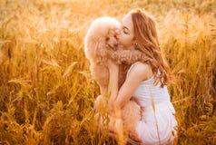 Chica joven con su perro en el campo en luz del sol Imágenes de archivo libres de regalías