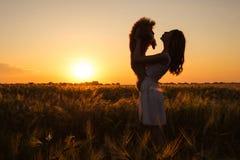 Chica joven con su perro en el campo en luz del sol Foto de archivo