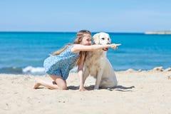 Chica joven con su perro por la playa Imagenes de archivo