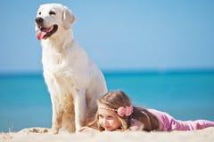 Chica joven con su perro por la playa Foto de archivo libre de regalías