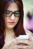 Chica joven con su teléfono móvil Fotos de archivo