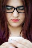 Chica joven con su teléfono móvil Foto de archivo libre de regalías