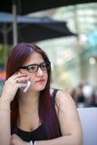 Chica joven con su teléfono móvil Imágenes de archivo libres de regalías