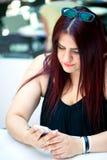 Chica joven con su teléfono móvil Fotografía de archivo libre de regalías