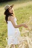 Chica joven con trigo conmovedor del sombrero del heno en un campo Imagenes de archivo