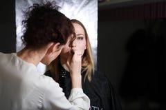 Chica joven con un artista de maquillaje foto de archivo libre de regalías
