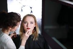 Chica joven con un artista de maquillaje fotos de archivo libres de regalías