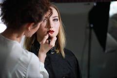 Chica joven con un artista de maquillaje imagenes de archivo