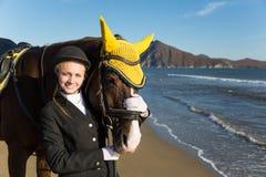 Chica joven con un caballo preferido en la playa. Fotos de archivo